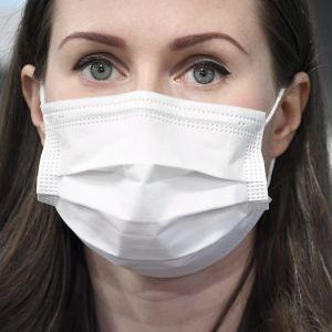 Närbild på en kvinna i munskydd.