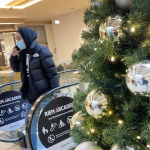 Bilden är tagen i ett köpcenter. Närbild på en julgran med lampor och silvriga stora julgransbollar. I bakgrunden ser man en rulltrappa som andänds av en person med uppdragen huva och munskydd.