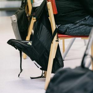 Reppuja roikkuu tuoleilla koululuokassa.