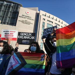 Personer som håller upp plakat och regnbågsflaggor under demonstration.