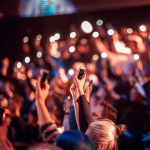 Ihmiset kädet ylhäällä, kännykät kädessä.