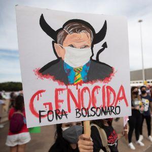 """Demonstrationer i Brasilien håller upp en skylt där det står """"folkmord Bolsenaro""""."""