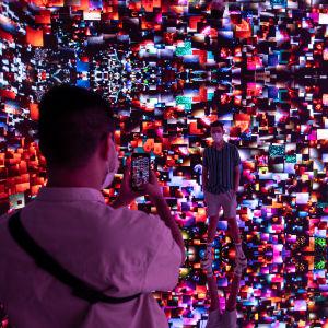 Människor fotograferar det digitala konstverket Machine Hallucination Space: Metaverse Lot 1, av Refik Anadol.