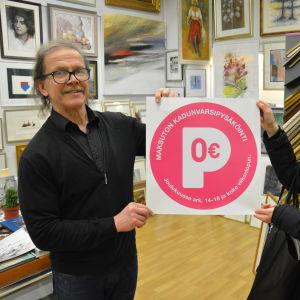 Rainer Lindewall och Hilla Inki håller upp en skylt med röd text: Parkering 0 euro.