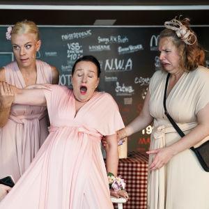 På bilden ses fyra festklädda kvinnor. En kvinna, i mitten, verkar ha ont och lutar sig mot en bänk samtidigt som hon hålls upp av de andra kvinnorna.