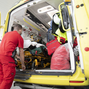 Förstavårdare lastar in en person i en ambulans.