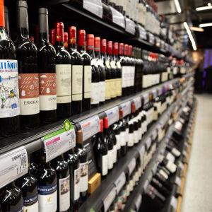 Alkon myymälän sisällä on hyllyssä punaviinipulloja, rivi jatkuu pitkänä. Kuvan tarkennus on lähimmissä olevissa pulloissa. Lähimpien pullojen kaarevista pinnoista erottuu sanat ATLANTICO ja ESPORAO. ATLANTICON hinta on 11.43 euroa.