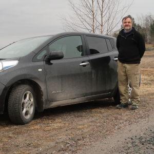 En man står framför sin elbil intill en åker i gråmulet väder.