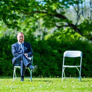 Löfven istuu tuolilla nurmikolla. Vieressä on tyhjä tuoli.