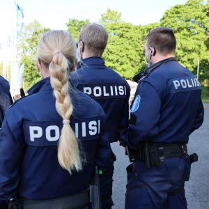 """Fyra poliser står på rad med ryggen mot kameran. På uniformen står det """"polis"""" på ryggen."""