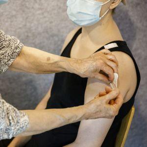 Nainen saa koronavirusrokotteen käsivarteensa.