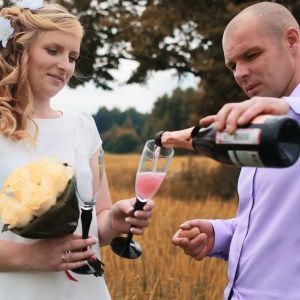 Ung man och kvinna i bröllopskläder står på äng och häller upp champagne i glas