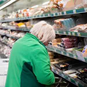 Lappeenrannan Prisman ruokakäytävällä työntekijä tarkastaa tuotteiden päiväyksiä.