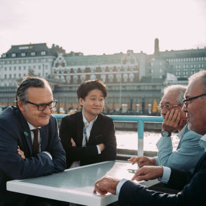 Four men engaged in a discussion over a table on the outside deck of a ferry outside Helsinki.