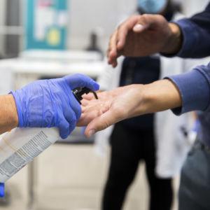 Närbild av händer då en person får desinfektionsmedel för händerna av en person i skyddshanskar. Personer ges desinfektionsmedel för händerna då de kommer in på ett sjukhus.