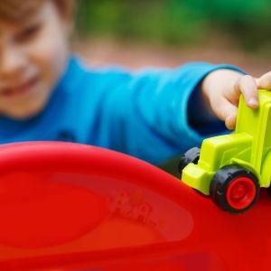 Barn leker med grön leksakstraktor i plast.
