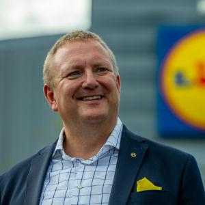Lidls vd Lauri Sipponen i bildens vänstermiljö och i bakgrunden företagets logotyp.
