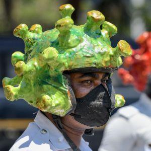 Två personer med coronavirushjälmar och munskydd.