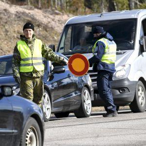 En beväring visar stopptecken för en bil.