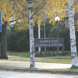En skylt där det står Närpes stad skymtar mellan två björkar i höstskrud..
