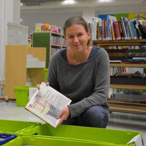 Kvinna sitter på huk framför en låda med böcker.