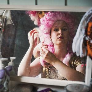Pianisti Sonja Hendunen katsoo peiliin pinkki perukki päässä, taustalla laulaja Noora Määttä.