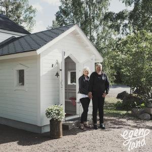 Man och kvinna står framför en väldigt liten, vitmålad träkyrka och håller varandra i handen.