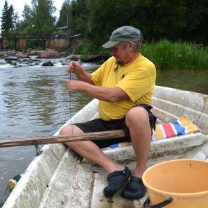 Man fiskar i roddbåt.