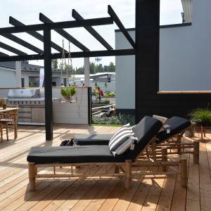 en stor terass med utomhusbord, grill och solstolar