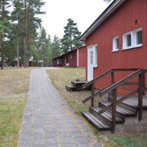 Röda stugor fungerar som inkvartering för deltagare som är på kurscentret högsand. Här syns röda stugor och tallar.