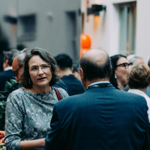 A woman and a man talking to each other during a mingle.