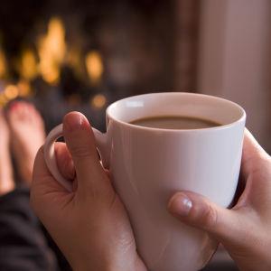höänder som håller i en kaffekopp, i bakgrunden en öppen spis