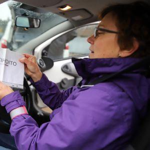Kotihoitaja Raija Riikonen esittelee pysäköintilappua.