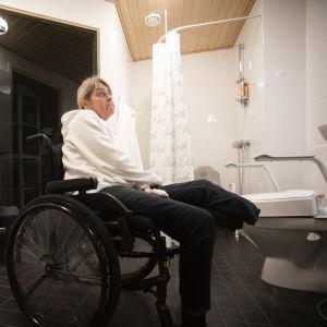 En kvinna sitter i en rullstol, inne i ett badrum. Hon ser uppgiven ut. I bakgrunden syns en dusch, en bastu och en toalettstol.