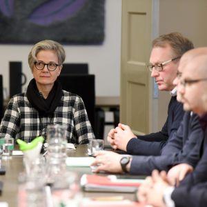 Sex personer sitter omkring ett bord, i mitten en dam i kort hår, glasögon och svart scarf.