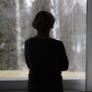 Tumma naisen hahmo katsoo ulos ikkunasta maisemaa.