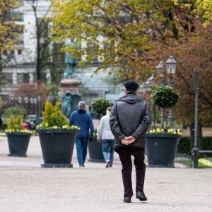Ett fåtal människor ute på promenad i Esplanadsparken i Helsingfors.