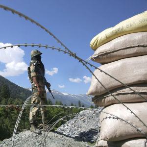 Sotilas seisoo kalliolla, etualalla piikkilankaa ja hiekkasäkkejä