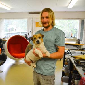 En man som håller en hund i famnen. I bakgrunden stolar.