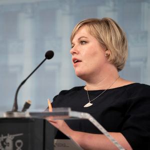 Annika Saarikko pitää puhetta sinertävän seinän edessä.