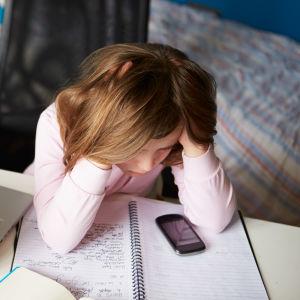 Tonåring tittar ner på sin mobiltelefon.