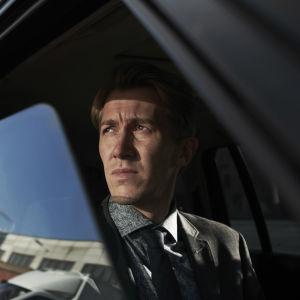 Pasi tittar ut genomen ett öppet bilfönster som speglar en fabrik.