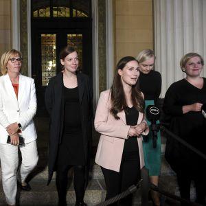 Regeringens kvintett och finansminister Matti Vanhanen står på rad på Ständerhusets trappa. Statsminister Sanna Marin talar i mikrofon.