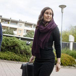 Statsminister Marin tittar bort från kameran. Hon har en svart klänning och en lila halsduk. Bredvid henne står Matti Niemi med ett munskydd och ser in i kameran.