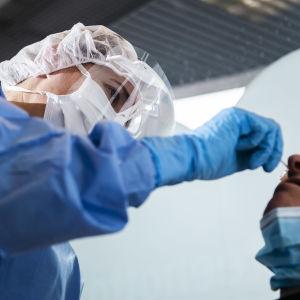 Sjukskötare i skyddsutrustning tar coronaprov på patient.