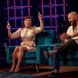 Arja Koriseva tuulettaa kädet ilmassa, Katja Ståhl ja Tero Vesterinen nauravat vieressä Elämäni Biisi -ohjelman sohvilla.