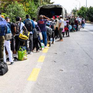 Ihmisiä matkatavaroineen jonossa tien laidalla