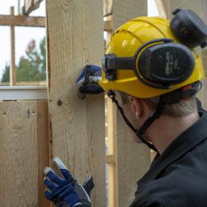 Byggnadsarbetare märker planka på bygge.