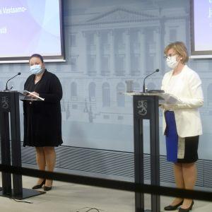 Sirpa Paatero, Krista Kiusu och Anna-Maja Henriksson iklädda munskydd står bakom var sitt podium.