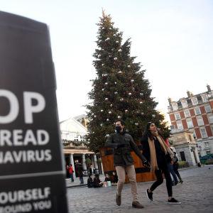 Bild på skylt där det står stoppa spridningen av coronaviruset, och i bakgrunden ett par som går hand i hand vid en stor julgran på julmarknad i London.